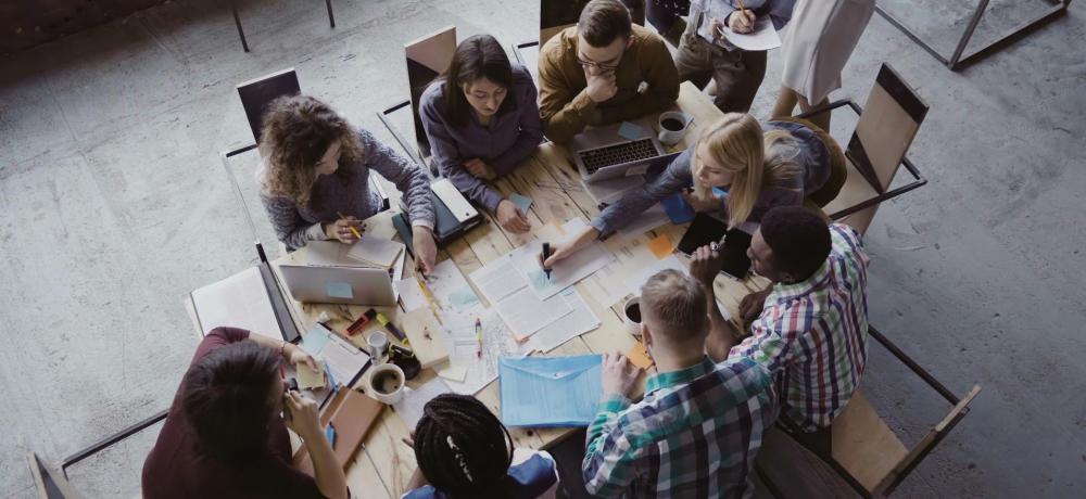 En grupp sitter och diskuterar och planerar vid ett bord.